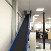 Incline powered conveyor to transport boxes up onto a mezzanine floor